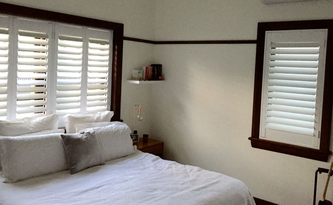 White plantation shutters with dark window frames and picture rails ...