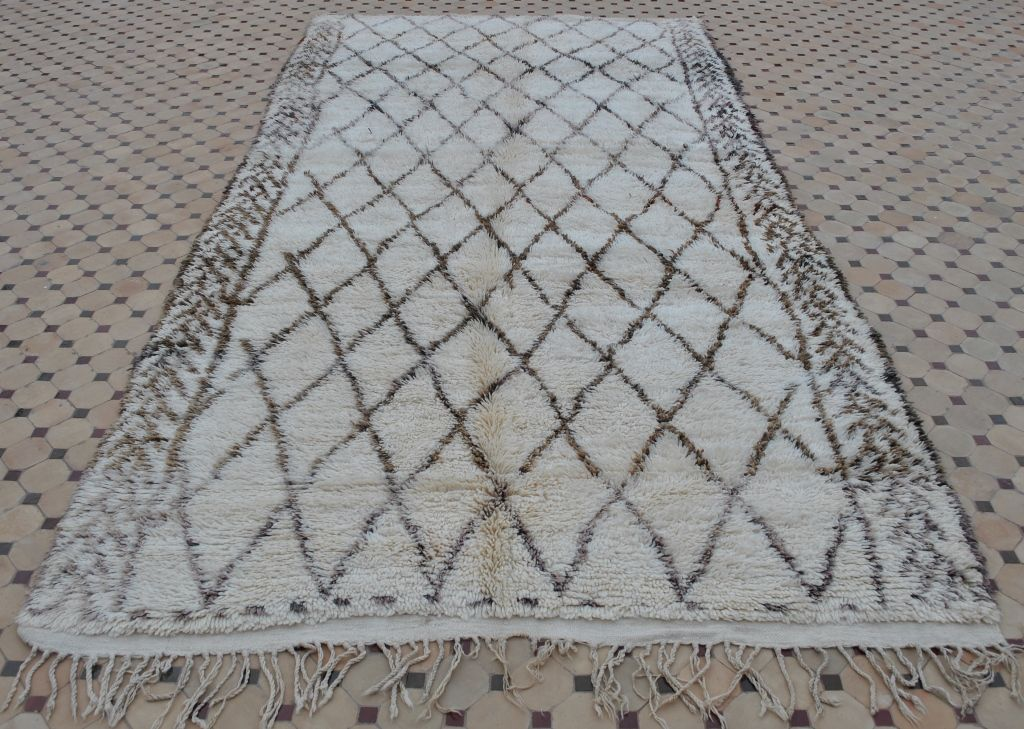 Very beautiful and gentle spirited vintage Beni Ouarain carpet densely knotted with a field in natural ivory. A network of slightly irregular female lozenges edged with patterned borders is knotted in taupe, silver grey and camel brown. The carpet is very nicely finished with a flatweave band on both ends and long fringes. Wonderfully soft underfoot! Medium pile, 100% wool. The carpet is in very good condition.
