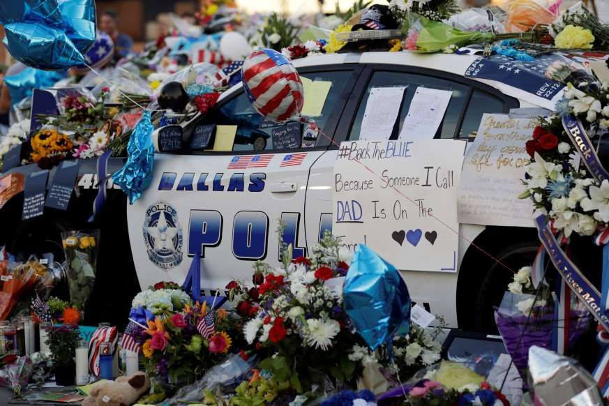 Notes, flowers and other items decorate a squad car at a
