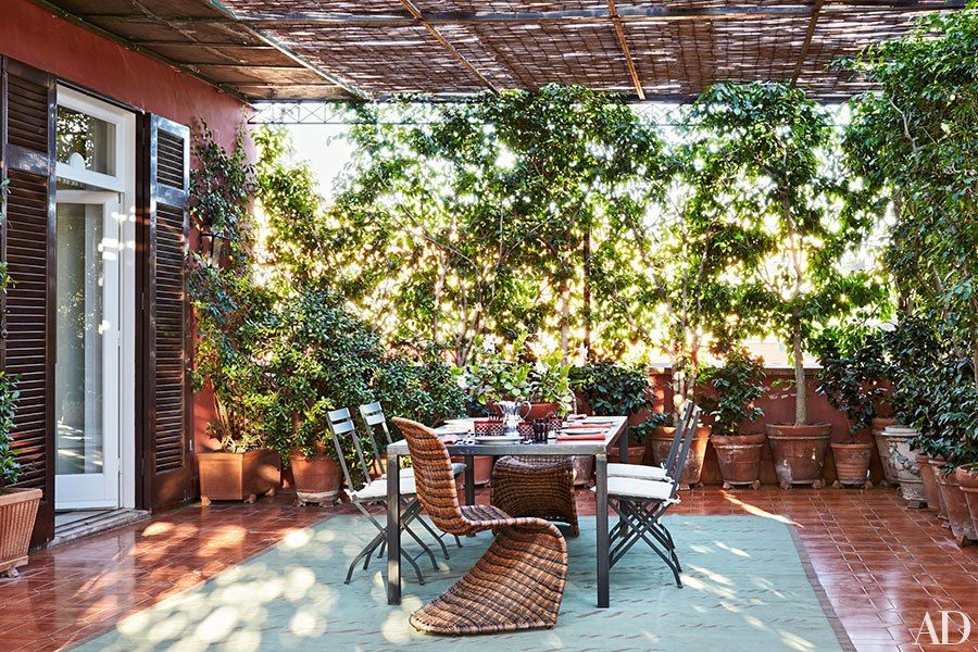 Shaded by a bamboo canopy, the terrace is furnished with Verner Panton rattan chairs and an Allegra Hicks carpet.