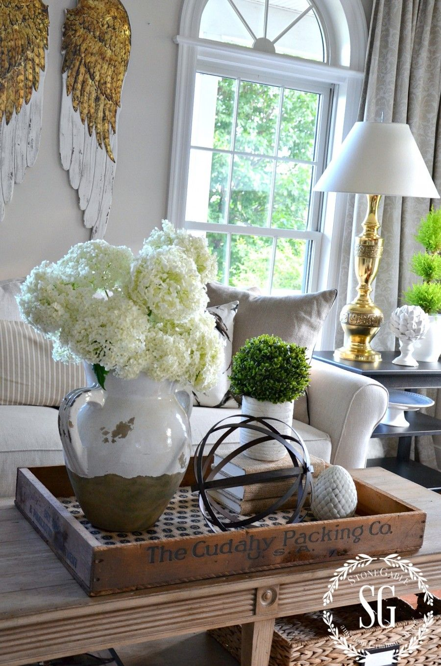I love the idea of putting the coffee table decor on a wooden tray Looks great and makes it easy to move out of the way when needed