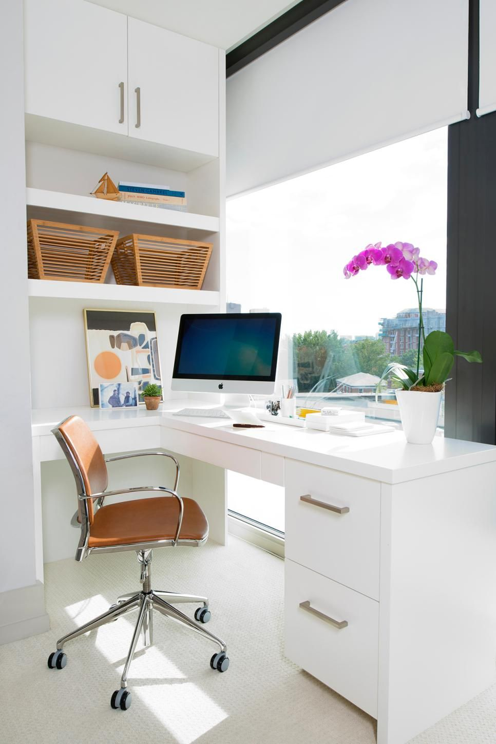 This sleek modern home office features a built in desk with plenty of storage and a large window to allow lots of natural light to fill the space