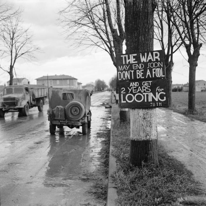 British Jeep Passes A Sign Warning Against Looting On The