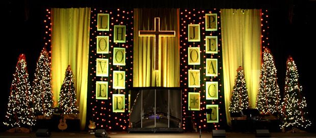 Christmas Stage Design With Words Lights And A Green Hue