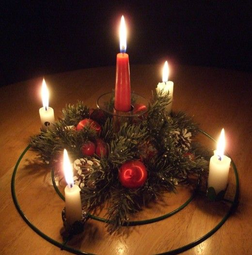 A Christmas Advent wreath with lit candles for Christmas Eve.