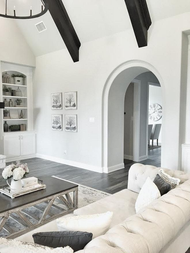The living rooms shelves display beautiful neutral farmhouse style decor art on the wall is from joss and main