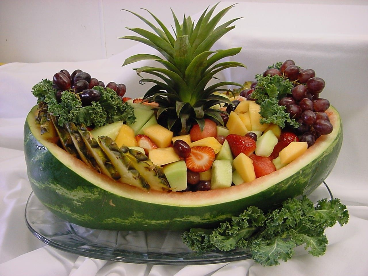 Watermelon cuts into boat design and topped with fruits