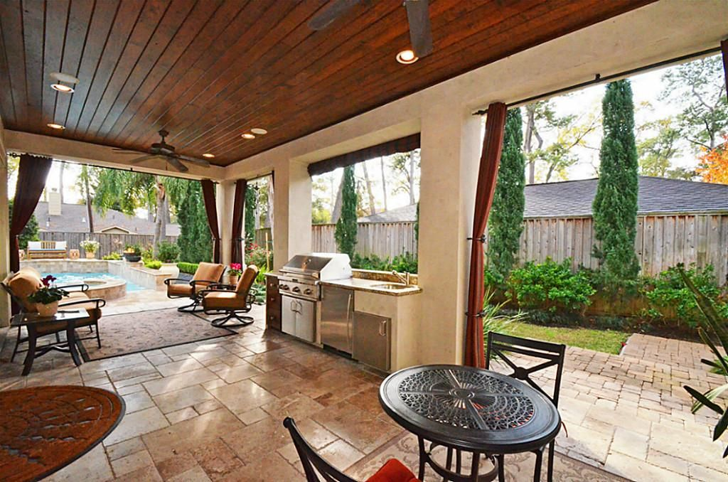 The Covered Patio And Outdoor Kitchen Are Adjacent To Family Room Travertine Tile Floors Stained Wood Plank Ceilings Add Charm Of E