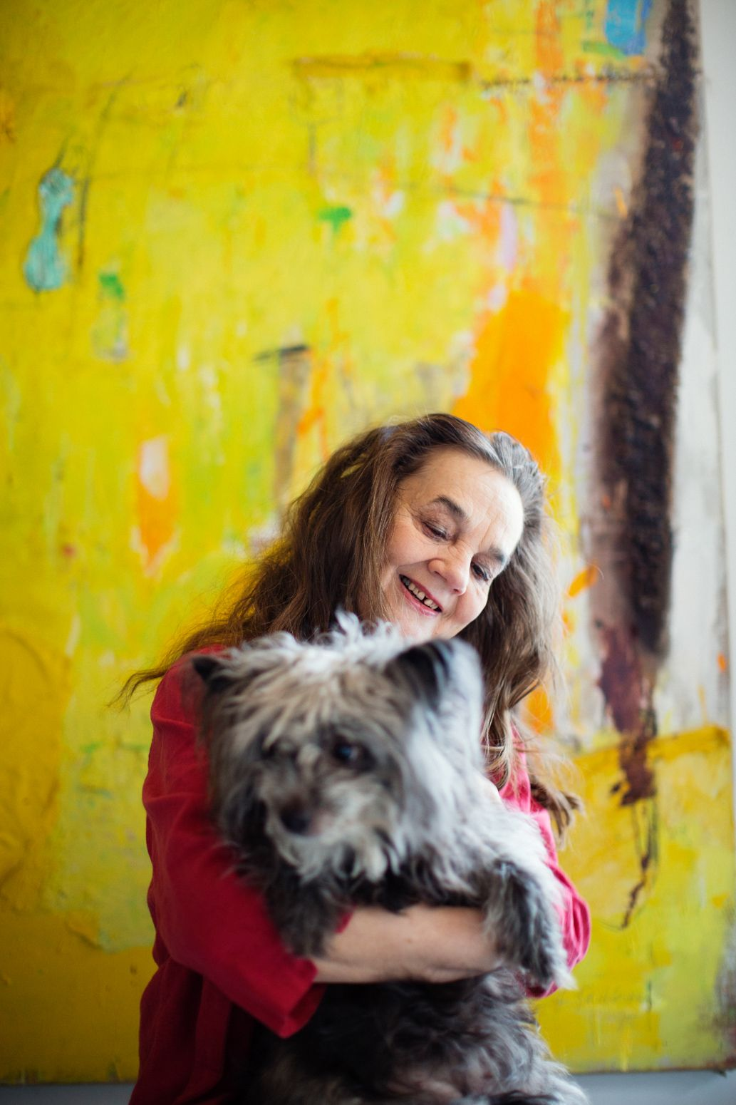 Happy. Portrait. Yellow Wall. Rugged Dog. Woman. Red Shirt. Photo by Pia Inberg.
