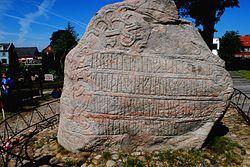 Skriftsiden af Den Store Jellingsten. Jellingmonumenterne er en samlet betegnelse for Jelling Kirke, Jellingstenene og de to kæmpegravhøje i Jelling. Jelling Monumentet blev 1994 optaget på UNESCOs Verdensarvsliste, fordi det afspejler den første officielle overgang fra hedenskab til kristendom i Skandinavien. Jellingstenene afspejler overgangen fra den hedenske vikingetid til den kristne middelalder. Den mindste runesten er ældst, formentlig fra ca. 935. Den er rejst af kong Gorm den Gamle…