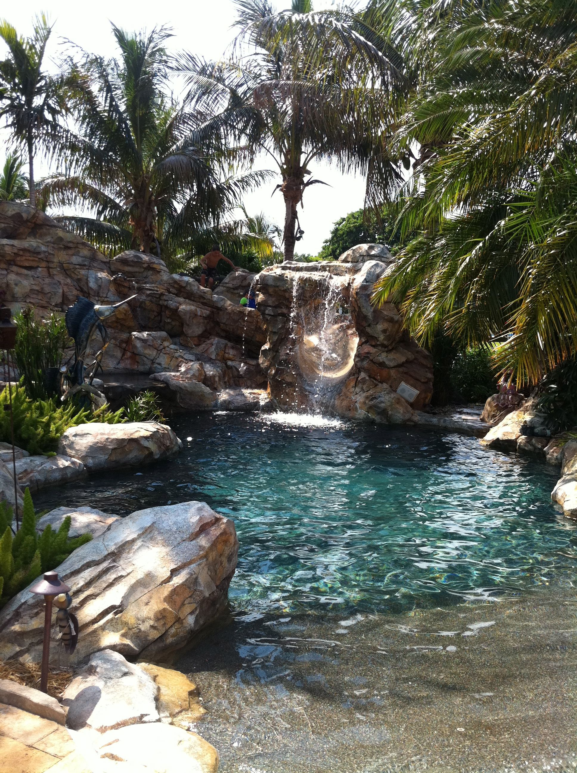 Lagoon backyard pool with beach entry man made boulders rocks and