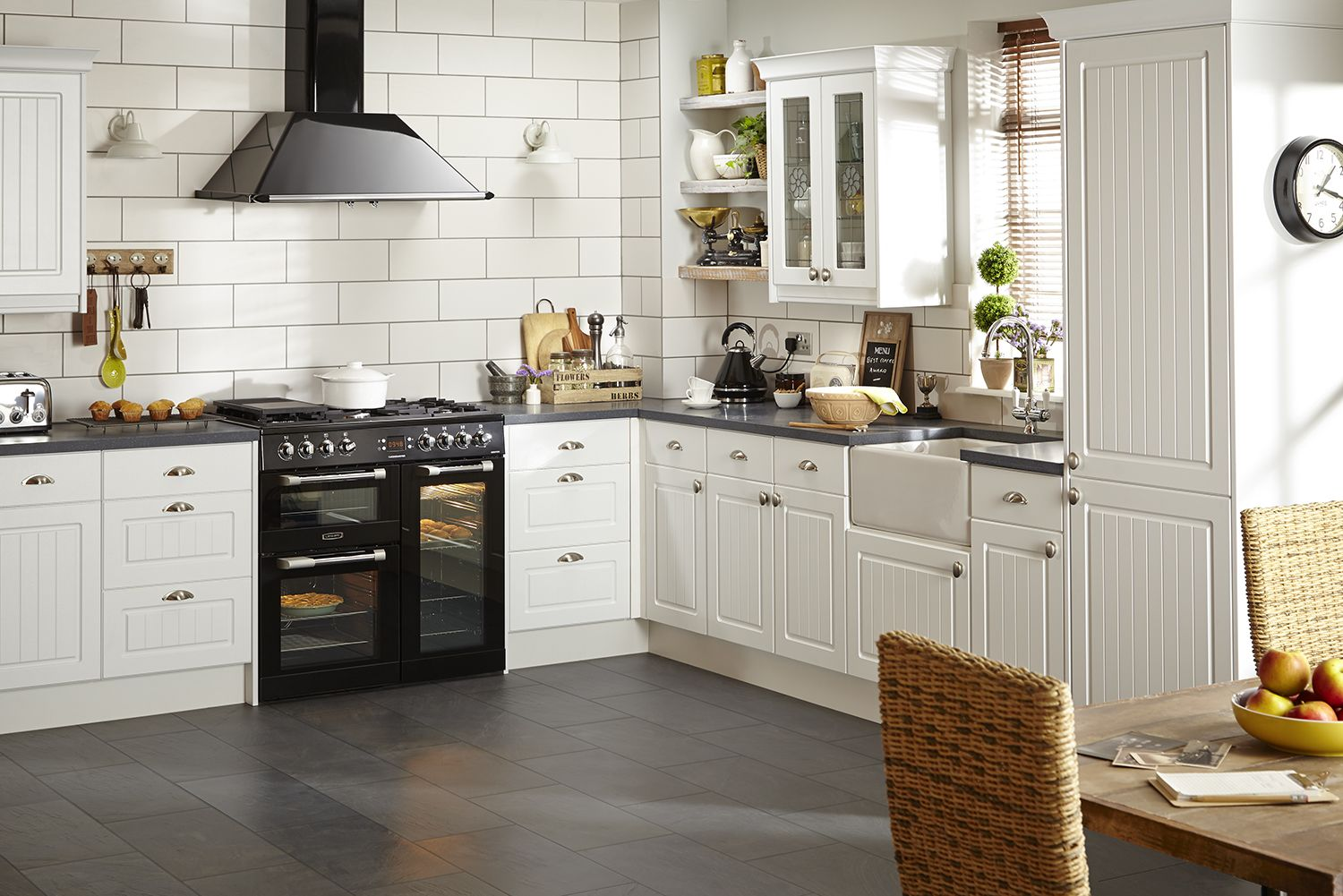 Combining bold, graphic black appliances and worktops with white kitchen  units brings country style kitchens