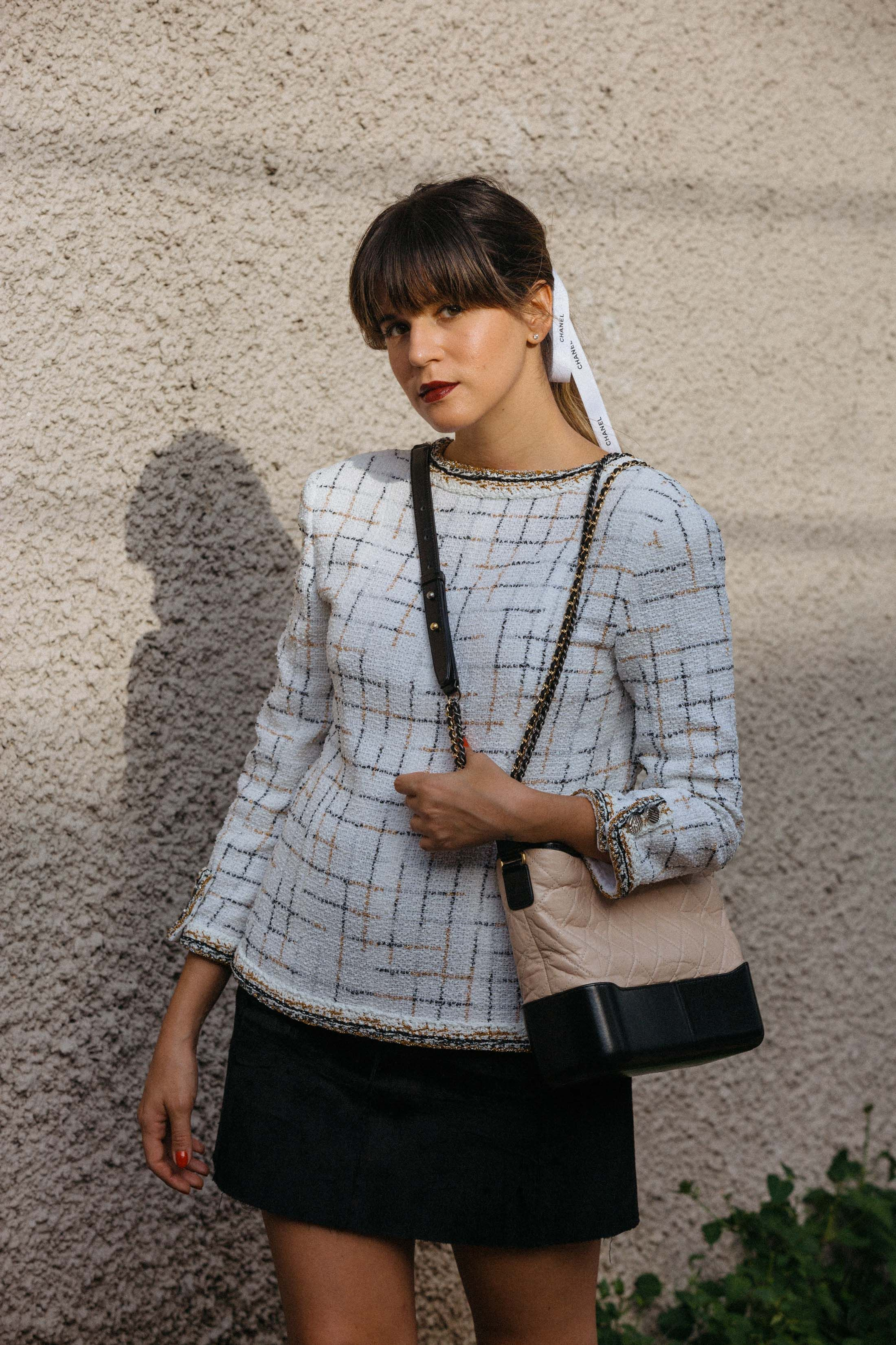 ce6835f106f697 Maristella styles her bangs with a ponytail and Chanel ribbon and wears the Chanel  Gabrielle bag in the V style
