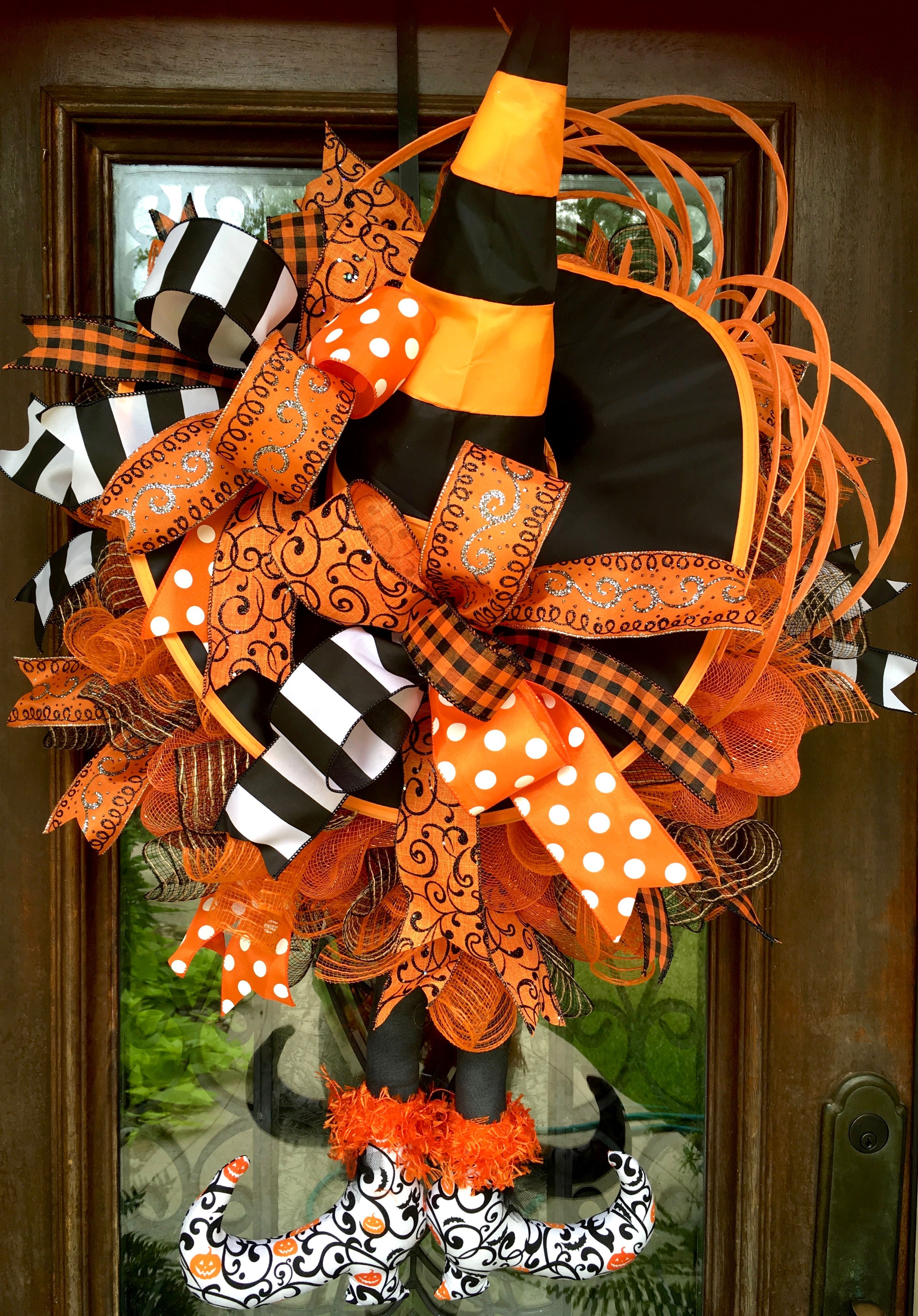 Orange and black witch halloween wreath with hat and legs