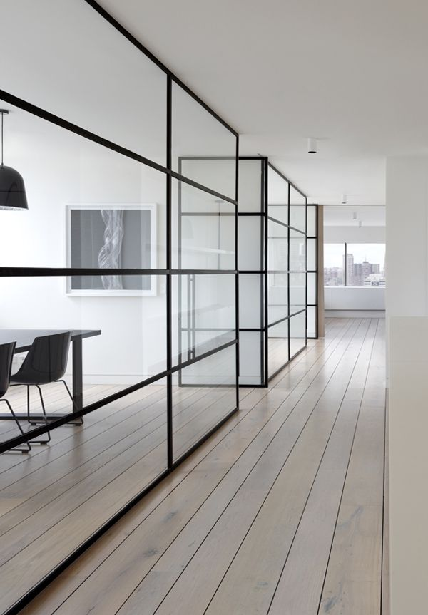 Glass walls with wide black panes for office spaces that ...