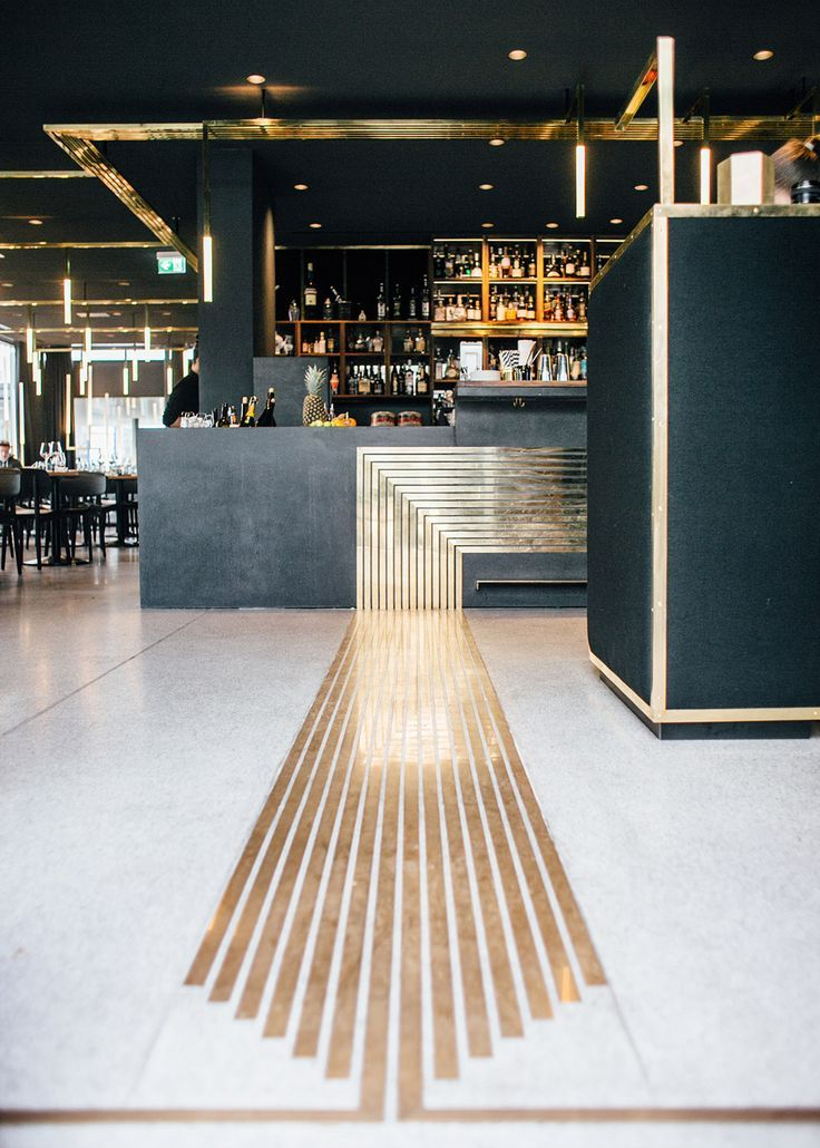 Modern bar design with metallic gold details on the floor and ...