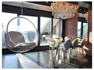 Hanging bubble chair & chandelier in an urban dining room.