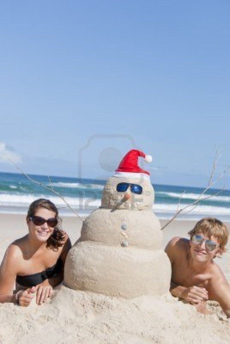 Pretty couple having fun at beach with perfectly build snowman ...