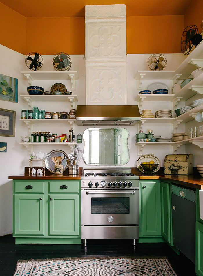 love the green cabinets and open shelving in this kitchen; jolts