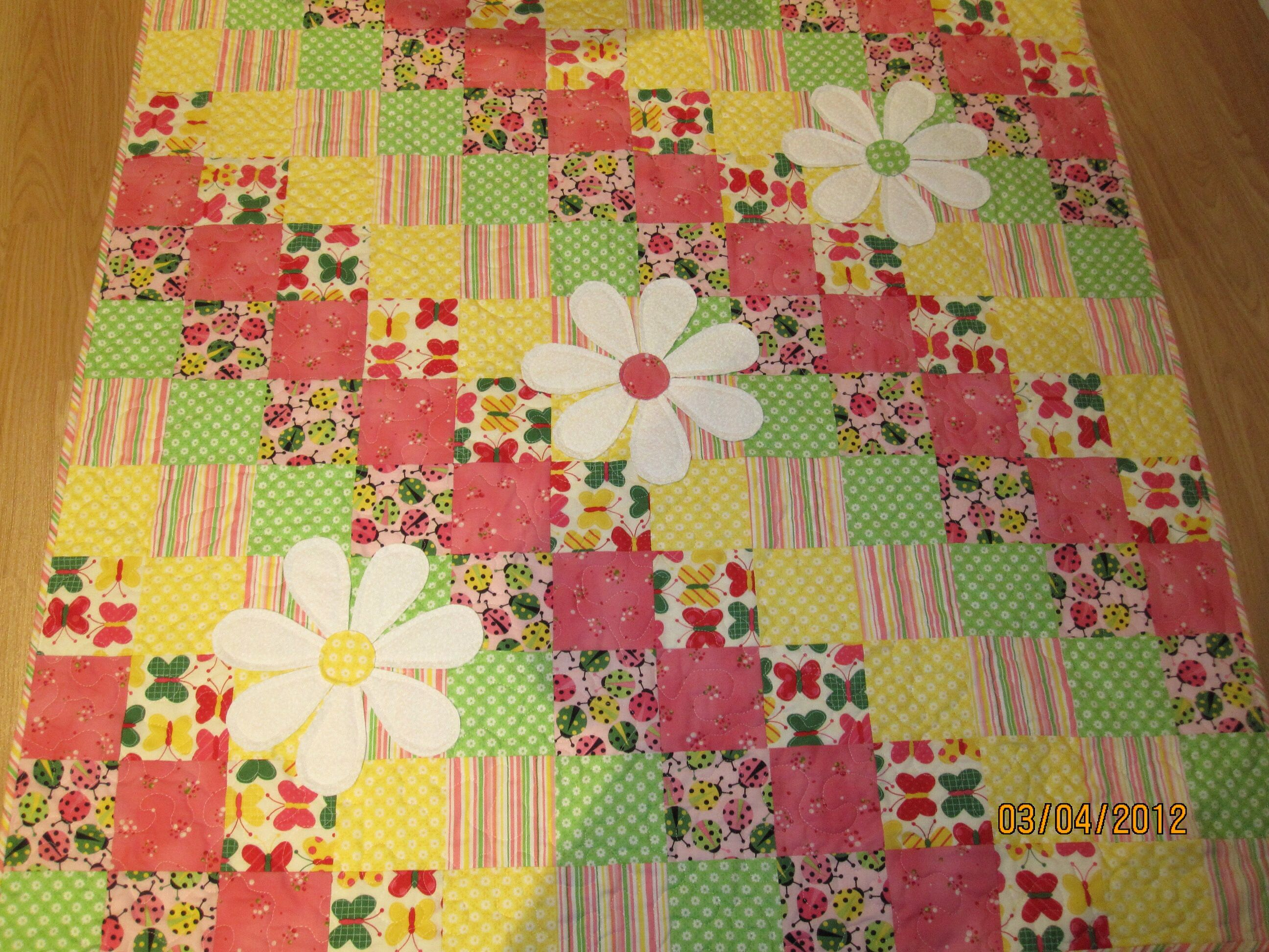 I made this quilt for my niece's baby girl. Each petal of the daisy was made double sided, rights sides together, clipped along the top curve and then turned right side out so the raw edges were inside the petal. They were sewn individually to the quilt top. The centre circle was done the same way and added to cover the ends of the petals.