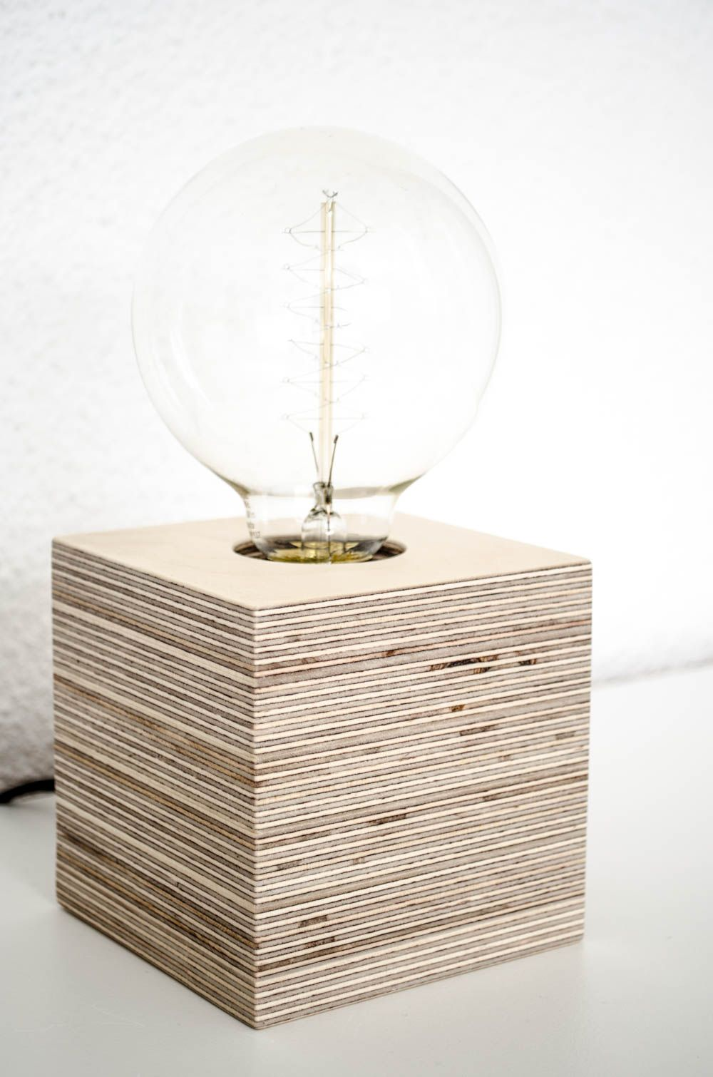 This relatively small lamp takes up an area of only 10 x 10 cm, making it ideal for many uses – including a desk, bed lamp, side table or even a book shelf. Built from sheets of birch plywood… More