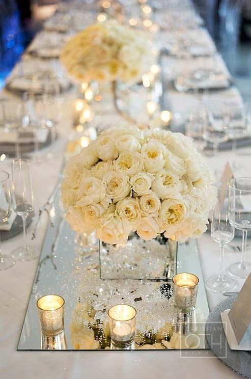 Beautiful white roses, Swarovski Elements and mercury votive holders reflect off a long mirrored runner on this wedding dinner table.