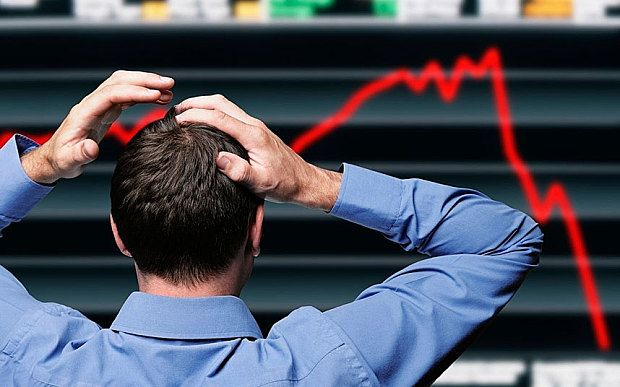 Stock Trader Clutching His Head in Front of a Screen Showing a Stock Market Crash