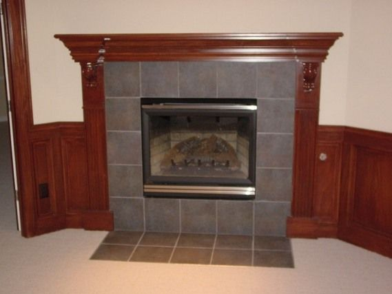 Gray tile and wood surround simple corner fireplace Fireplace