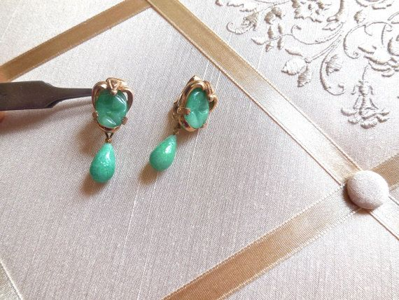 Vintage 50s Peking glass drop earrings in green Jade glass, clip on. Please zoom in for details. These earrings are unmarked but very good quality. The central piece of glass is carved and prong set in gold tone metal with a tear drop of glass dangling. The earrings measure 1 1/4 long by 1/2 at widest point. In excellent vintage condition, stones in tact, no chips or cracks and clips tight.  Please review store policies prior to purchasing  Thanks for your interest*  Also visit my o...