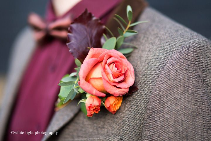 Dark brown suit with a cranberry shirt + orange rose boutonniere