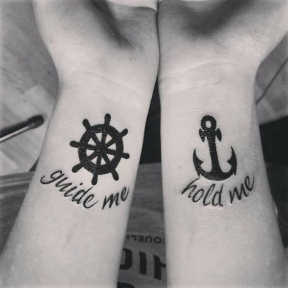 An anchor and wheel couple tattoo. As these two go together they are a perfect fit for couple tattoos. There are also words etched on the e wrists saying quotes that also reflect what the symbols are for.: