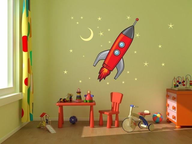 une fusée et des étoiles jaunes collées au mur vert pâle dans la chambre bébé