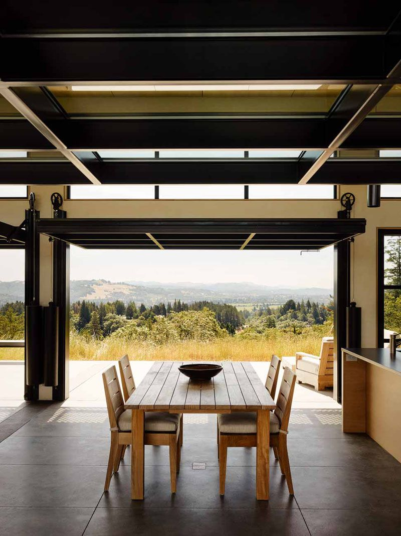 Large glass paneled doors on a pulley system open this dining room to the outdoors