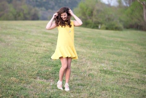 Fun yellow dress with a ruffled flounce hem worn with white lace wedges that tie up the ankle.