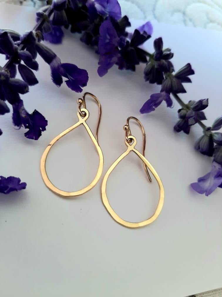 """""""Lots of pizzazz, but graceful and classic in style. Easy on your earlobes but large and bright enough to really show up, this pair of solid 18k hammered gold french hook earrings are super comfortable for those of us with small earlobes but want a \""""big earring\"""" look at times. Minimalist design with that unmistakable hand crafted look. Great dress up earrings as the subtle texture and high polish catch the light well. They move gracefully and turn different directions. Good proportion of size"""
