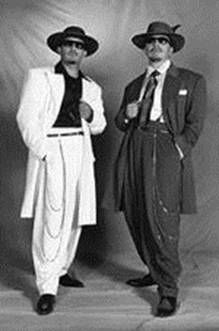 The zoot suit was epitome of men's fashion during the 1920's. The jacket was designed with shoulder pads and wide lapels. You can see on these two figures an overly long watch chain hangs from the waist. The pants were baggy in cut and then became tighter at the ankle.