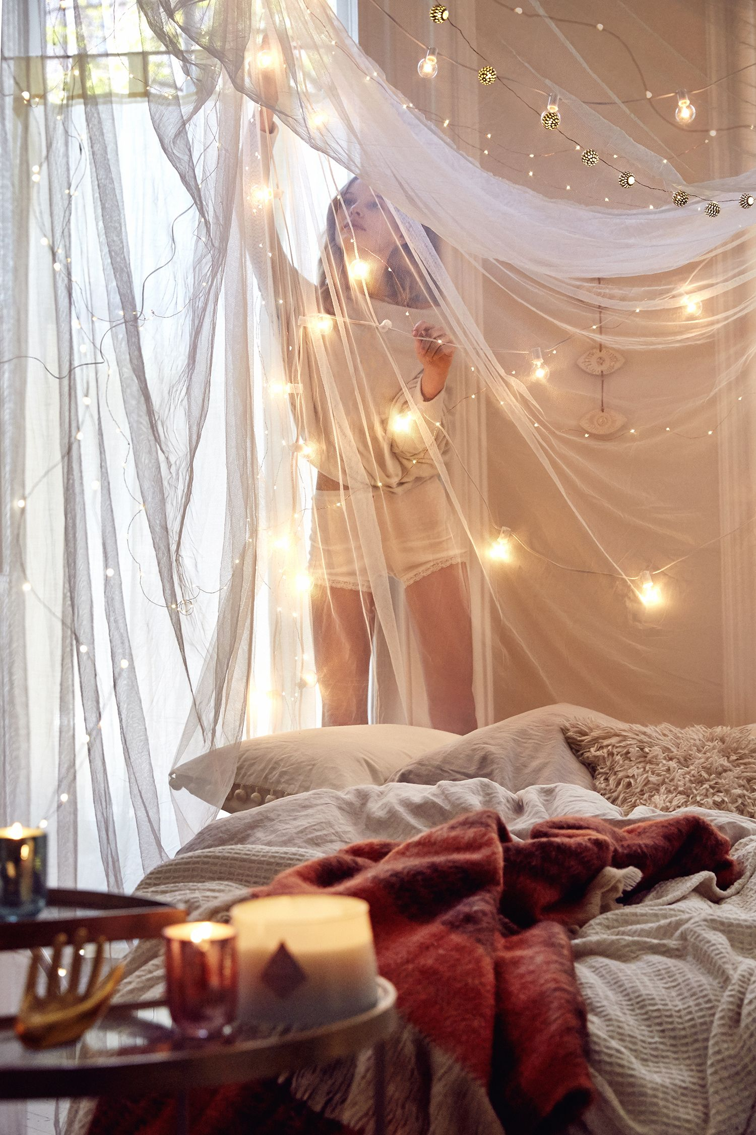 Draped fairy lights, draped canopy, red touch on bed with ...