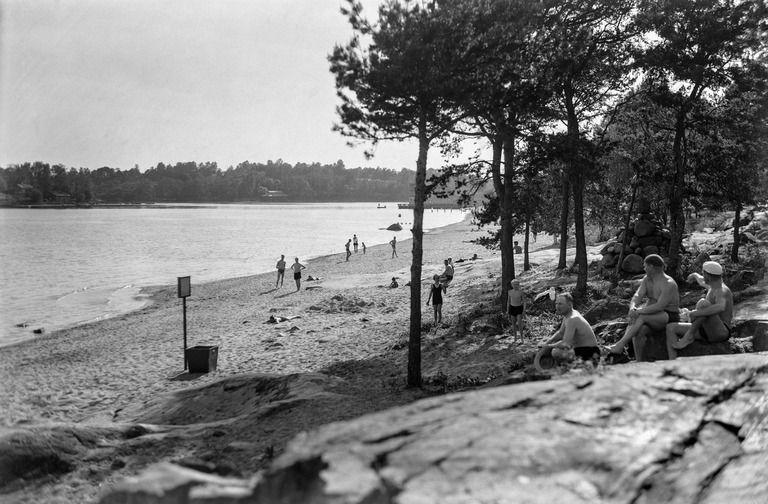 Mustikkamaa, uimaranta. Ihmisiä kalliolla ja hiekkarannalla....