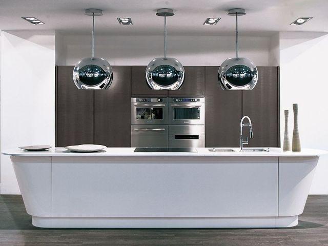 un îlot de cuisine blanc et ovale et trois suspensions métalliques