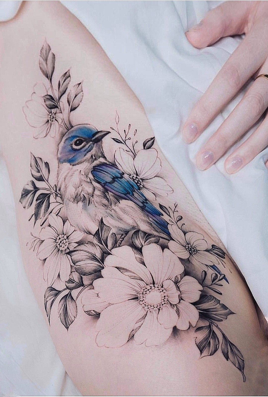 Photo of In floral tattoos, all but one of the flowers are black and white.
