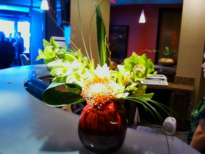 Simple arrangement using protea and two sprays of cymbidium orchids.