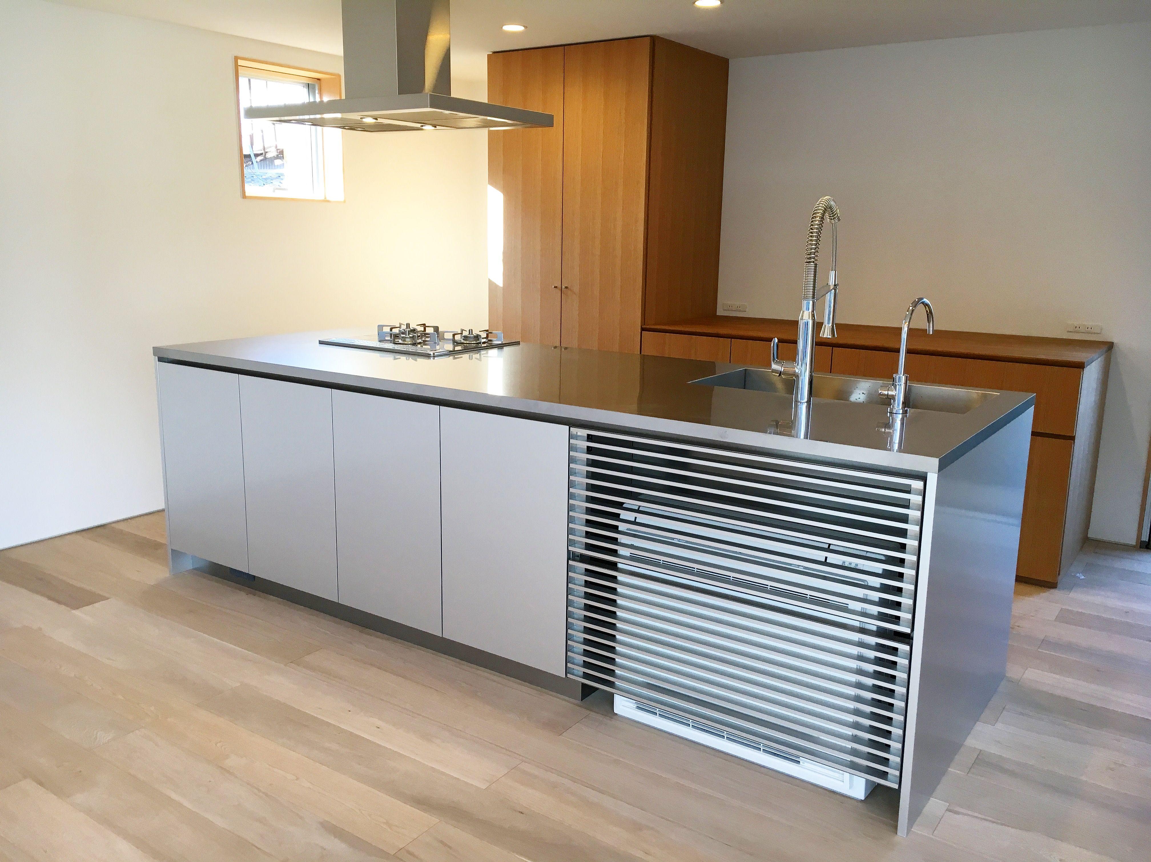 施工事例 アイランドキッチン メタルのアイランドキッチンです ポイントは何と言ってもステンレスとアルミで特注製作した床置き式エアコン前のルーバーです キッチン全体のデザインを崩さないように細かな寸法まで計算して設計しています 他にも機器を多く