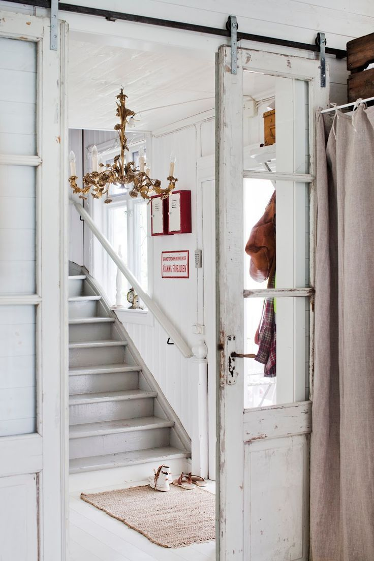 VINTAGE Windowed Doors on sliding tracks give this space an airy open look. Shabby whites!