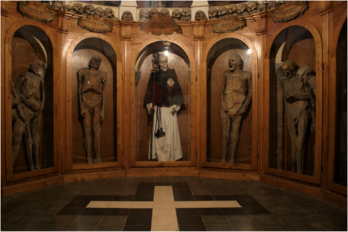 La Chiesa dei Morti, The Church of the Dead, is located in Urbania in Italy. Inside lies the Cemetery of the Mummies, which was built in 1833. This cemetery is famous for its strange phenomenon of natural mummification.