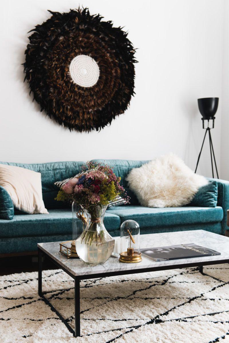 nina schwichtenbergs wohnzimmer mit turkisem samtsofa als eyecatcher wandbild aus federn marmortisch in schwarz