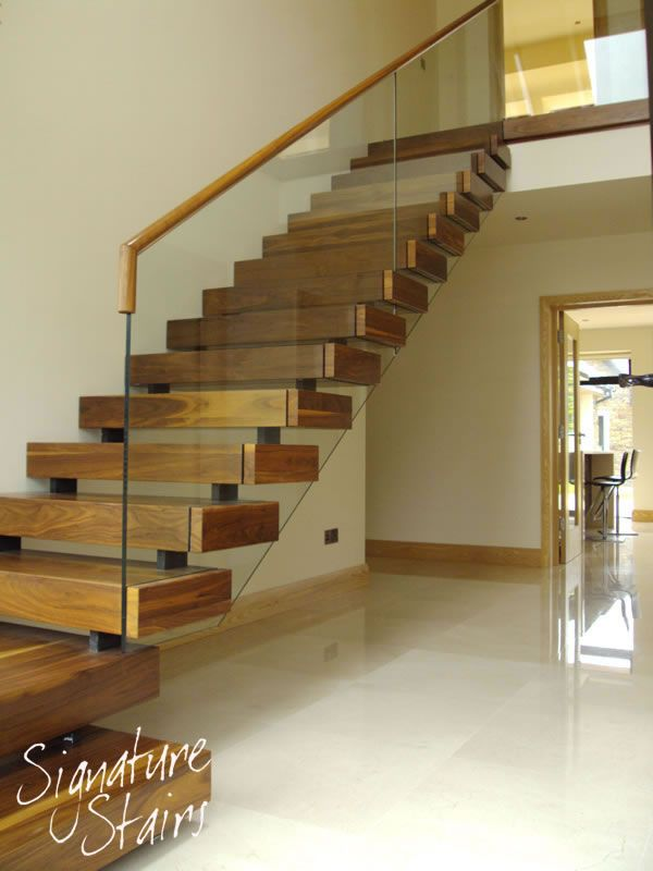 This staircase has an almost floating step effect with open rise steps and off-set stringer support. Each step is clad in high grade natural wood and the staircase is finished with a toughened glass balustrade with rebated matching timber handrail.