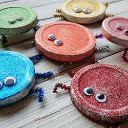 Use recycled jar lids and glitter paint to create these fun bugs, just in time for Earth Day!