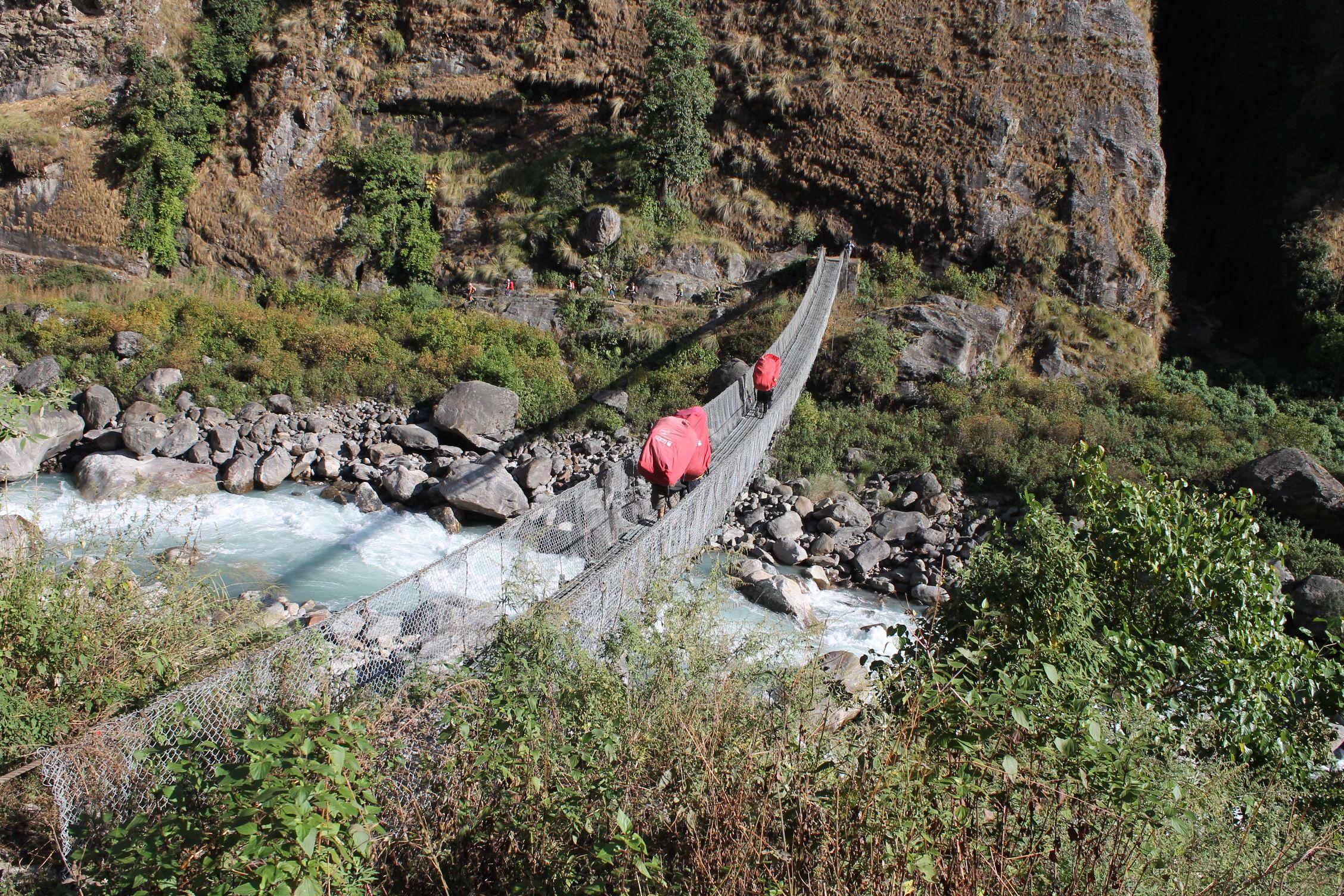 Porteadores con 35 kg a la espalda cruzando el puente como si nada