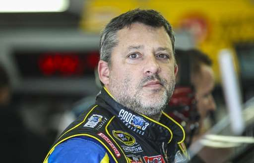 Driver Tony Stewart waits in the garage while his car is