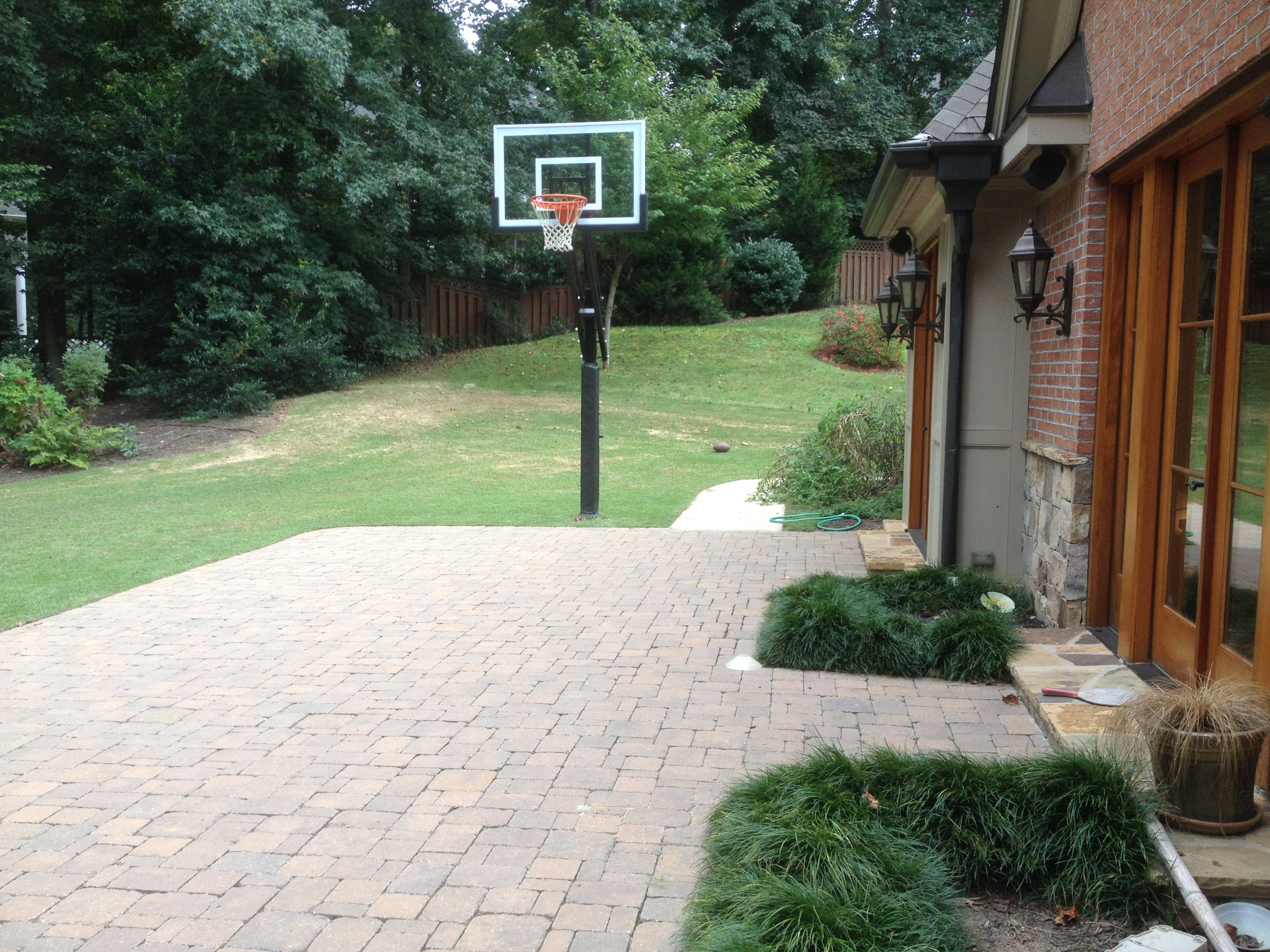 A Pro Dunk Silver Basketball System Compliments The End Of This Cobbled Brick Backyard Slab